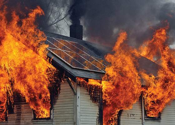 Photo of burning house with solar panels on roof